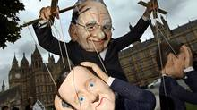 A demonstrator dressed in a Rupert Murdoch mask controls puppets of British Prime Minister David Cameron (foreground) and British Minister for Culture, Media and Sport Jeremy Hunt, (right) during a protest against Mr. Murdoch's proposed takeover of BSkyB. (ADRIAN DENNIS/AFP/Getty Images)