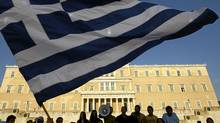 Protesters raise a Greek flag in front of parliament during a rally in Athens last summer against austerity measures, a scene that's been repeated many times since. (© John Kolesidis / Reuters/REUTERS)