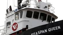 A worker paints the Seaspan Queen tugboat undergoing maintenance at Washington Marine Group Shipyards in North Vancouver, B.C., on Feb. 2, 2011. (Darryl Dyck for The Globe and Mail)