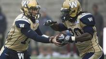 Winnipeg Blue Bombers' quarterback Max Hall, left, hands off to Will Ford during first half CFL football action against the Montreal Alouettes in Montreal, Monday, October 14, 2013. (Graham Hughes/THE CANADIAN PRESS)
