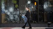 An employee of a looted shop cleans up debris in the aftermath of riots in the Clapham area of London Tuesday, Aug. 9, 2011. (Elizabeth Dalziel/Elizabeth Dalziel/AP)