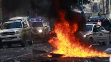 A pile of rubbish set on fire by striking municipal workers burns in Cape Town, with police vehicles in the background, on Aug. 16, 2011. (NARDUS ENGELBRECHT/AFP/Getty Images)