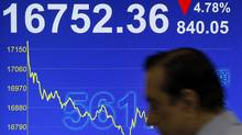 A man walks past a screen displaying the Hong Kong stock index's movement at a stockbrokerage firm in Hong Kong on Monday, Oct. 3. (Vincent Yu/Vincent Yu/Associated Press)