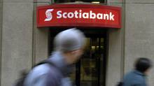 Pedestrians walk past a Bank of Nova Scotia location in downtown Toronto. (Louie Palu/The Globe and Mail)
