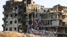 Children play in front of damaged buildings in the Arabeen neigbourhood of Damascus on July 21, 2013. (REUTERS)
