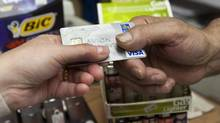 A consumer pays with a credit card at a store July 6, 2010 in Montreal. (Ryan Remiorz/THE CANADIAN PRESS)