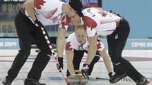 Canada's skip Brad Jacobs (C) delivers a stone as teammates Ryan Harnden (L) and E.J. Harnden sweep during their men's curling round robin game against China in the Ice Cube Curling Centre at the Sochi 2014 Winter Olympic Games February 16, 2014. (INTS KALNINS/REUTERS)