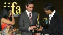 Bollywood actor Vivek Oberoi, right, presents the International Indian Film Academy (IIFA) trophy to Dalton McGuinty, Premier of Ontario, as fellow Bollywood actor Celina Jaitley looks on during a function in Mumbai, India, Wednesday, Dec. 9, 2009. The IIFA announced that the 2011 awards will be held in Toronto, Ontario. (Rafiq Maqbool/AP Photo/Rafiq Maqbool)