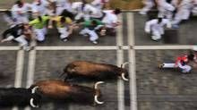 Revelers run on Estafeta street beside to El Pilar fighting bulls ranch, during the fourth running of the bulls at the San Fermin fiestas, in Pamplona northern Spain, Tuesday, July 10, 2012. (AP Photo/Alvaro Barrientos) (Alvaro Barrientos/AP)