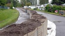 A temporary dyke is set up down the middle of Farrell Street to help protect homes from flood waters due to high water levels on the Fraser River in Prince George, B.C., June 8, 2012. Residents in homes on the right side of the street have been given evacuation notices (Brent Braaten/THE CANADIAN PRESS)