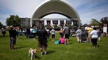 Mourners watch as blankets with photos of deceased dogs are raised during a memorial in Langley, B.C., on Sunday June 22, 2014. Charges have been laid against a dog walker from Langley, B.C., who is accused of leaving six dogs to die in a hot truck. (CP)