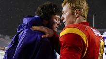 University of Calgary Dinos' quarterback Andrew Buckley, right, pats Western University Mustangs quarterback Will Finch on the shoulder after winning the CIS Mitchell Bowl in Calgary, Alta., Saturday, Nov. 16, 2013. The Dinos defeated the Mustangs 44-3 and will face Laval in the Vanier Cup. (JEFF MCINTOSH/THE CANADIAN PRESS)