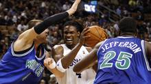 Toronto Raptors forward Chris Bosh drives to the basket against Minnesota Timberwolves' Oleksiy Pecherov, left, and Al Jefferson in Toronto, December 8, 2009. (MARK BLINCH)