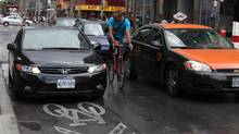 """A cyclist yells at the driver of an illegally parked car during rush hour in Toronto that the bike lane """"isn't a parking spot."""" Separated bike lanes can prevent this kind of incident and make cyclists feel safer. (Deborah Baic/The Globe and Mail)"""