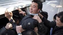 Wang Junwei a protester outside the newspaper office Southern Weekend is taken away by undercover police in Guangzhou January 10, 2013. (John Lehmann/The Globe and Mail)