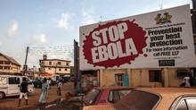 "People pass a banner reading ""STOP EBOLA"" in the city of Freetown, Sierra Leone, on Friday. (Aurélie Marrier d'Unienville/AP)"