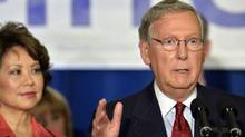 Mitch McConnell with his wife Elaine Chao, following his victory in the Republican primary, Tuesday, May 20, 2014, at the Mariott Louisville East in Louisville, Kentucky. (Timothy D. Easley/AP)