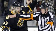 Referee Kevin Pollock, right, signals as Boston Bruins' Patrice Bergeron (37) celebrates after making the winning goal in a shootout against the Nashville Predators during an NHL hockey game in Boston, Saturday, Feb. 11, 2012. The Bruins won 4-3. (AP Photo/Michael Dwyer) (Michael Dwyer/AP)
