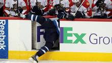 Kenndal McArdle of the Winnipeg Jets goes flying into the Florida Pantherss bench in NHL action at the MTS Centre on Thursday night. (Marianne Helm/2011 Getty Images)