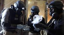 A U.N. chemical weapons expert, wearing a gas mask, holds a plastic bag containing samples from one of the sites of an alleged chemical weapons attack in the Ain Tarma neighbourhood of Damascus in this August 29, 2013 file photo. (STRINGER/REUTERS)