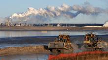 Workers use heavy machinery in the tailings pond at the Syncrude oil sands facility near Fort McMurray, Alta. (MARK RALSTON/Mark Ralston/AFP/Getty Images)
