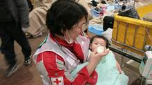 In this photo released by Japanese Red Cross Society, a baby survivor is fed milk by a member of Japanese RC's National Disaster Response Team at the Ishinomaki Red Cross Hospital in Ishinomaki in Miyagi Prefecture (state), Saturday, March 12, 2011, one day after the catastrophic earthquake and tsunami hit northeastern Japan. (Toshiharu Kato/AP/Toshiharu Kato/AP)