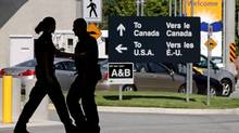 Canadian border guards are silhouetted as they replace each other at an inspection booth at the Douglas border crossing on the Canada-USA border in Surrey, B.C., on August 20, 2009. An internal report from the Canada Border Services Agency shows Canada's border guards are pulling out their guns, batons and pepper spray less often. THE CANADIAN PRESS/Darryl Dyck (DARRYL DYCK/THE CANADIAN PRESS)