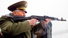 Russian designer Mikhail Kalashnikov, the creator of the world's most famous assault rifle, the AK-47, aims a current version of his weapon. (STR/STR/AP)