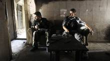 Members of the Free Syrian Army sit on a sofa inside a house in the old city of Aleppo June 19, 2013. (MUZAFFAR SALMAN/REUTERS)