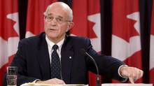 Retired Supreme Court justice Frank Iacobucci points to a report in Ottawa on Oct.21, 2008. (Adrian Wyld/THE CANADIAN PRESS)