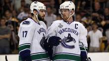 Ryan Kesler,left, of the Vancouver Canucks talks with teammate Henrik Sedin during Game 4 on June 8, 2011. (Elsa/Getty Images)