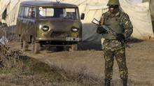 A Ukrainian soldier stands at a checkpoint near the village of Salkovo, near the Crimean border, March 10, 2014. A pro-Russian force opened fire in seizing a Ukrainian military base in Crimea on Monday and NATO announced reconnaissance flights along its eastern frontiers as confrontation around the Black Sea peninsula showed no sign of easing. (VALENTYN OGIRENKO/REUTERS)
