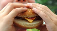 Child eating a burger in a stock photo. (Thinkstock)