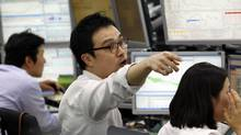 A currency trader works at the foreign exchange dealing room of the Korea Exchange Bank headquarters in Seoul, South Korea, Thursday, Sept. 22, 2011 (Lee Jin-man)