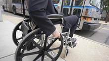 Disabled man in wheelchair by bus. (Photos.com)