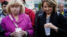 MPP Parkdale-Highpark Cheri DiNovo (left) and Peggy Nash NDP candidate in Parkdale-High Park (right) hold candles during a moment of silence during a vigil in Toronto on Sunday June 3, 2012. (Michelle Siu/THE CANADIAN PRESS)
