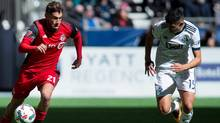 Toronto FC midfielder Jonathan Osorio moves the ball while being chased by Vancouver Whitecaps midfielder Matias Laba during a March 18 game. TFC looks to extend its franchise-record win streak to seven Friday when it visits the New York Red Bulls. (DARRYL DYCK/THE CANADIAN PRESS)