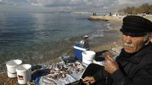 A fisherman waits to sell his fish at a beach in Flisvos, a suburb west of Athens on Feb. 15, 2012. Many Greeks are suffering huge cuts in their living standards, leading some people to believe an economic catastrophe for Greece is already under way. (YIORGOS KARAHALIS/Yiorgos Karahalis/Reuters)