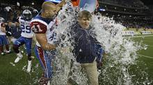 Montreal Alouettes head coach Dan Hawkins, Shea Emry (41) and Chip Cox (11) celebrate their win over the Winnipeg Blue Bombers after their CFL game at Investors Group Field in Winnipeg Thursday, June 27, 2013. (John Woods/THE CANADIAN PRESS)