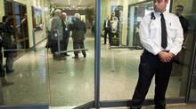 A security guard stands watch at the McGill University Health Centre offices (MUHC) in Montreal, Tuesday, September 18, 2012, where members of Quebec's anti-corruption squad conducted a raid at the premises. (Graham Hughes/THE CANADIAN PRESS)