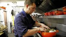 Chef Michael Caballo prepares food, including the chicken baked in hay, at Edulis restaurant (Deborah Baic/The Globe and Mail)