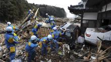 Rescue members seek survivors in Rikuzentakata, northern Japan, Monday, March 14, 2011, three days after a powerful earthquake-triggered tsunami hit the country's east coast. (Masamine Kawaguchi/AP Photo/The Yomiuri Shimbun, Masamine Kawaguchi)