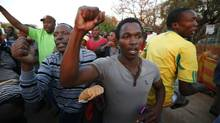 Miners and their supporters dance after being released outside the court in Ga Rankuwa, near Pretoria Sept. 3, 2012. Workers are marching on the Lonmin Marikana platinum mine again on Sept. 5, 2012. (MIKE HUTCHINGS/REUTERS)