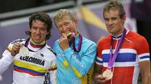 Kazakhstan's Alexandr Vinokourov bites the gold medal while posing for photographs with Rigoberto Uran of Colombia, left, silver, and Alexander Kristoff, right, with the bronze, after winning the Men's Road Cycling Race at the 2012 Summer Olympics, Saturday, July 28, 2012, in London. (AP)