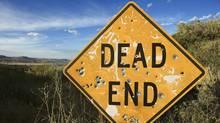 Dead end sign with bullet holes. (Ron Chapple/www.jupiterimages.com)