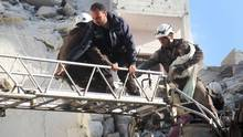 Syrian Civil Defence members evacuate a toddler from the rubble of buildings in Idlib, on May 31, 2016. (OMAR HAJ KADOUR/AFP/Getty Images)