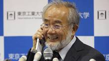 Nobel Prize winner Yoshinori Ohsumi smiles as he speaks with Japanese Prime Minister Shinzo Abe on a mobile phone. (Shizuo Kambayashi/Associated Press)