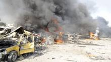 Smoke rises from the wreckage of mangled vehicles at the site of an explosion in Damascus on May 10, 2012. (Sana/Reuters)