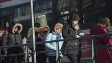 Pedestrians brave the cold as they get on a streetcar in Toronto during a cold snap across Southern Ontario on Jan. 7, 2014. (Aaron Vincent Elkaim/The Canadian Press)