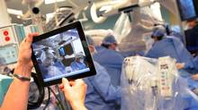 A nurse records progress on an iPad as surgeons operate on patient Paul Szasz in the Multi-Purpose Operating Room (MPOR) at Toronto General Hospital in Toronto, Ont. Feb. 13/2012. (Kevin Van Paassen/The Globe and Mail)